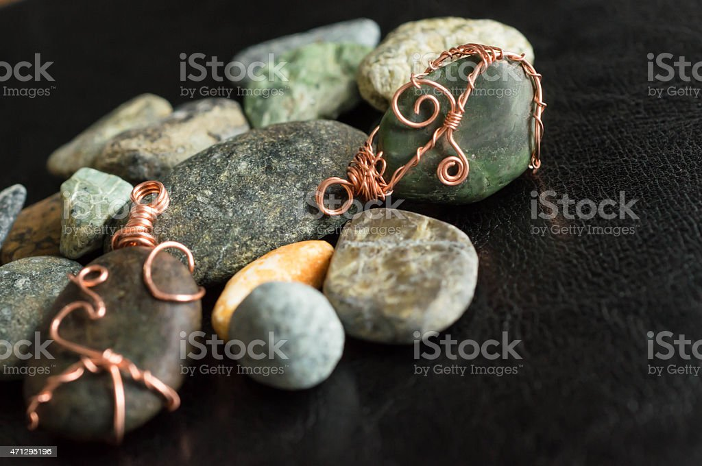 Two wire wrapped pendants among stones stock photo