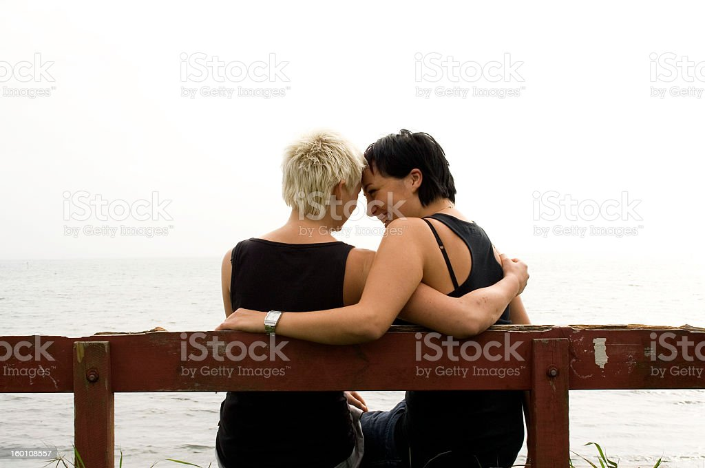 Two woman embracing each other on a beach front stock photo