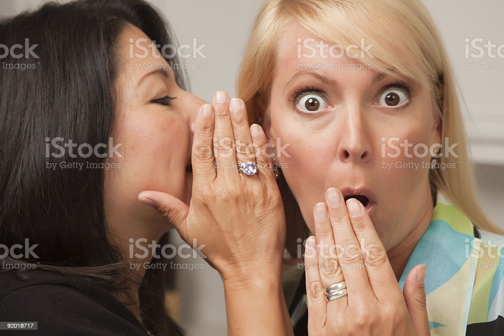 Two woman friends whispering secrets to one another royalty-free stock photo