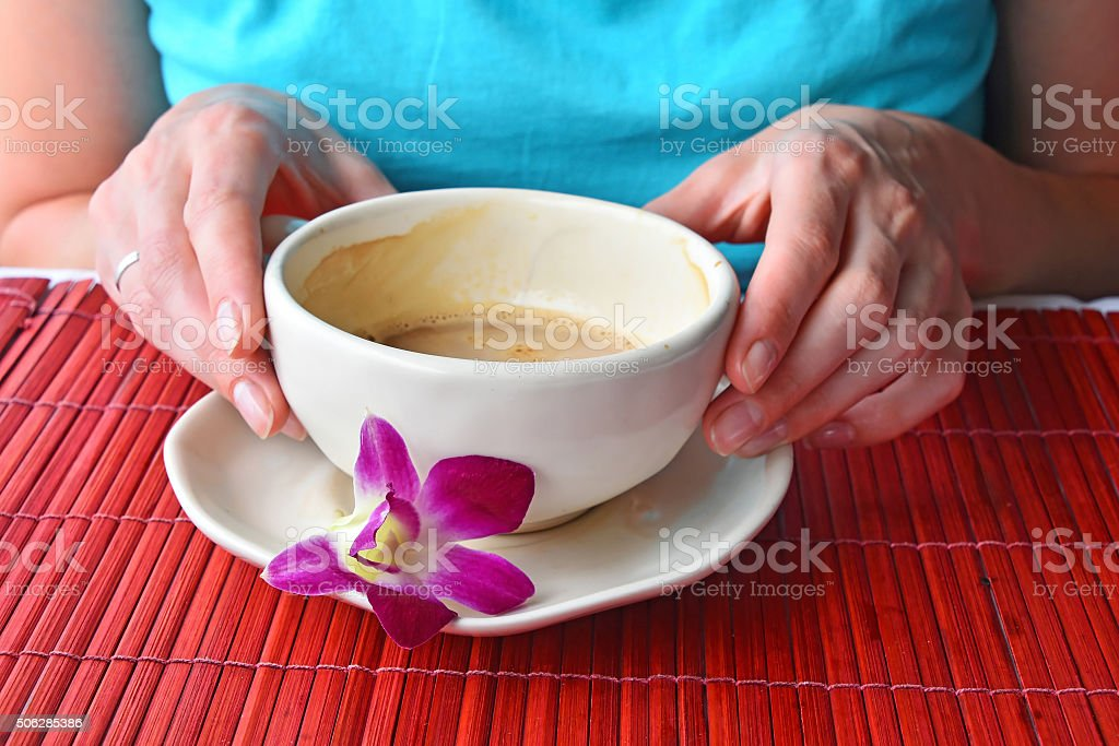 Two woman hands holding coffee cup with flower royalty-free stock photo