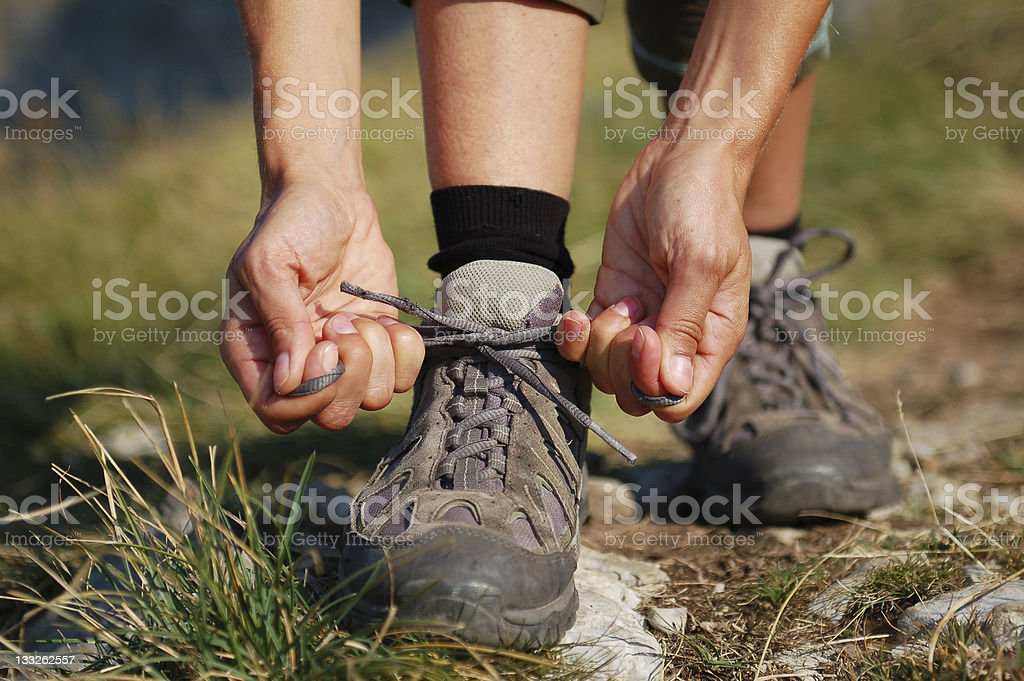 Two Woman Hands Lacing up Trekking Shoes stock photo