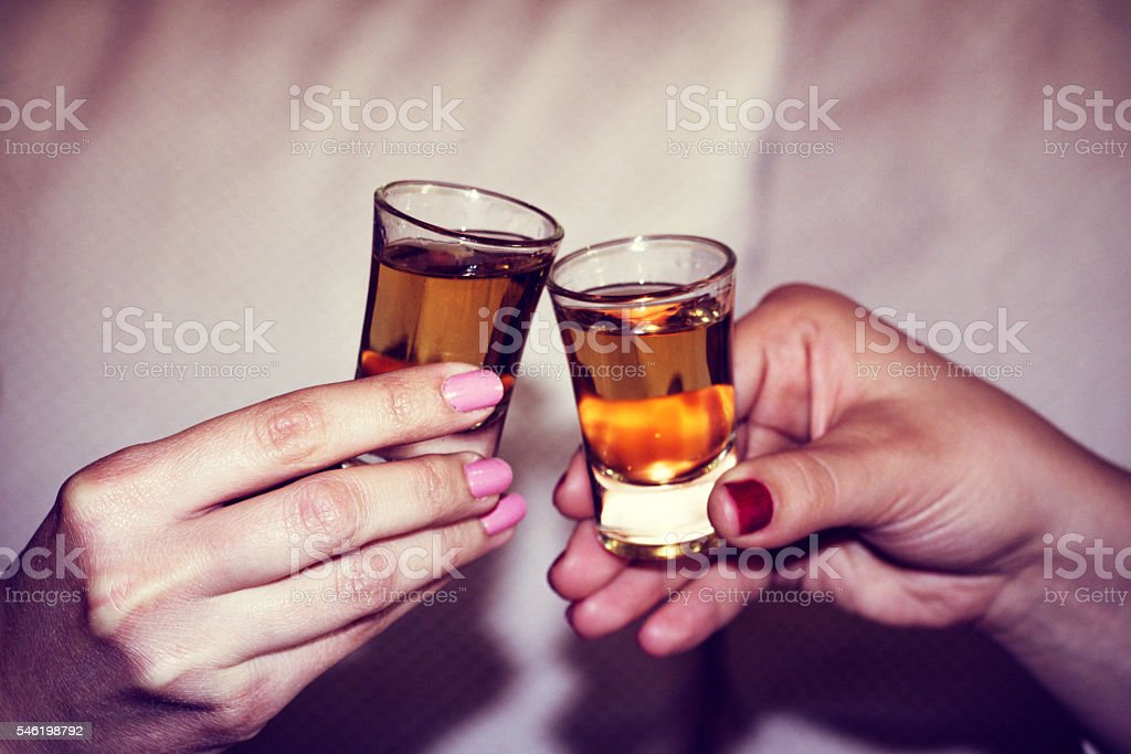 Two woman hands toasting whiskey, brandy with isolated backgroun stock photo