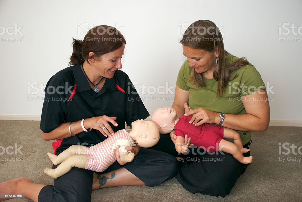 Two woman hold baby dummies so they can learn CPR stock photo