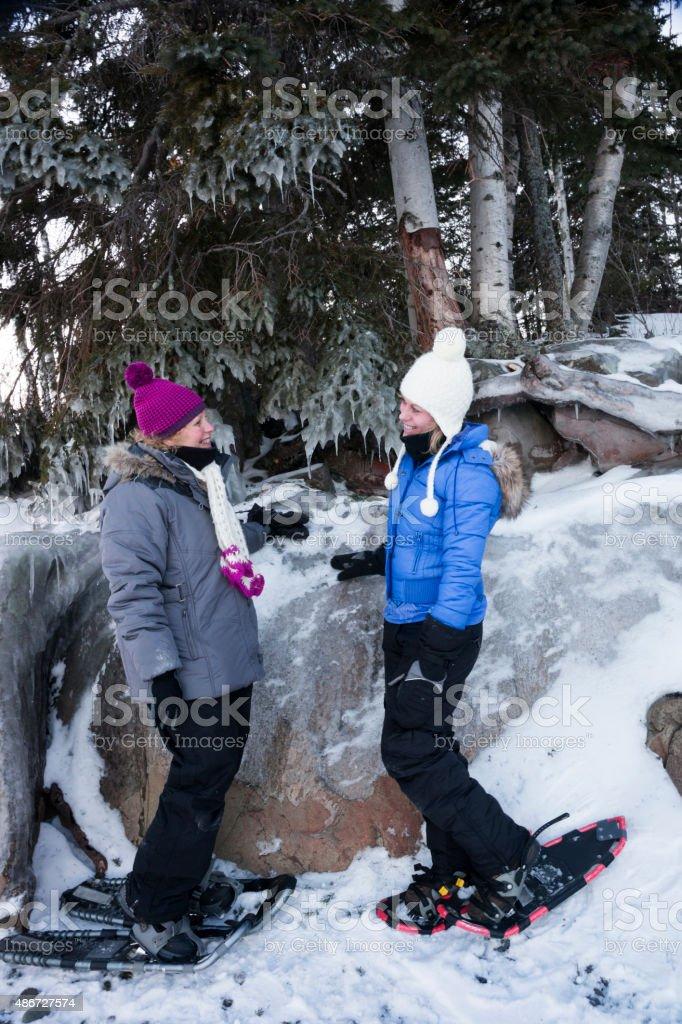 Two woman in snowshoes take a break stock photo