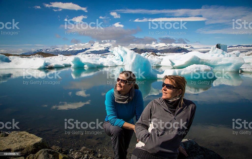 two woman on glacier lagoon Jokulsarlon in Iceland stock photo