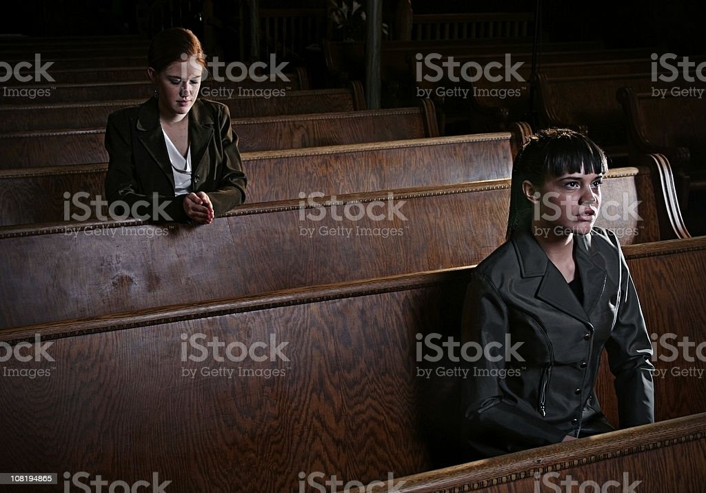 Two Woman Praying in an Old Church Cathedral. stock photo