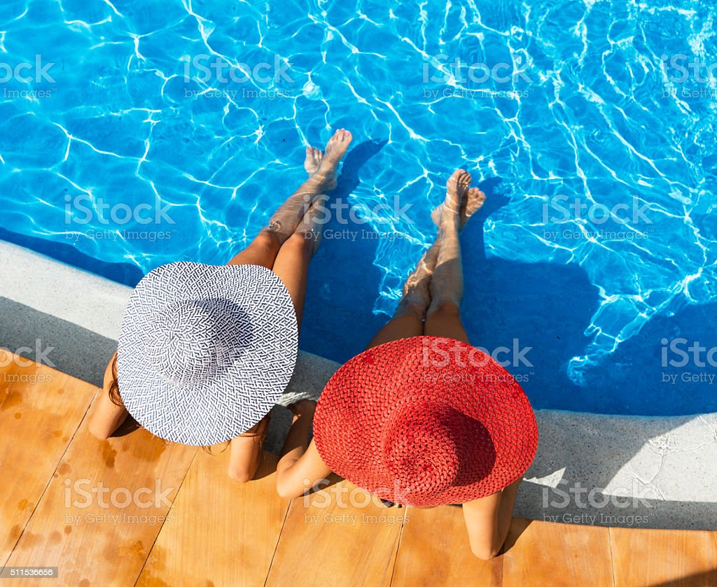 Two woman relaxing in a resort swimming pool stock photo