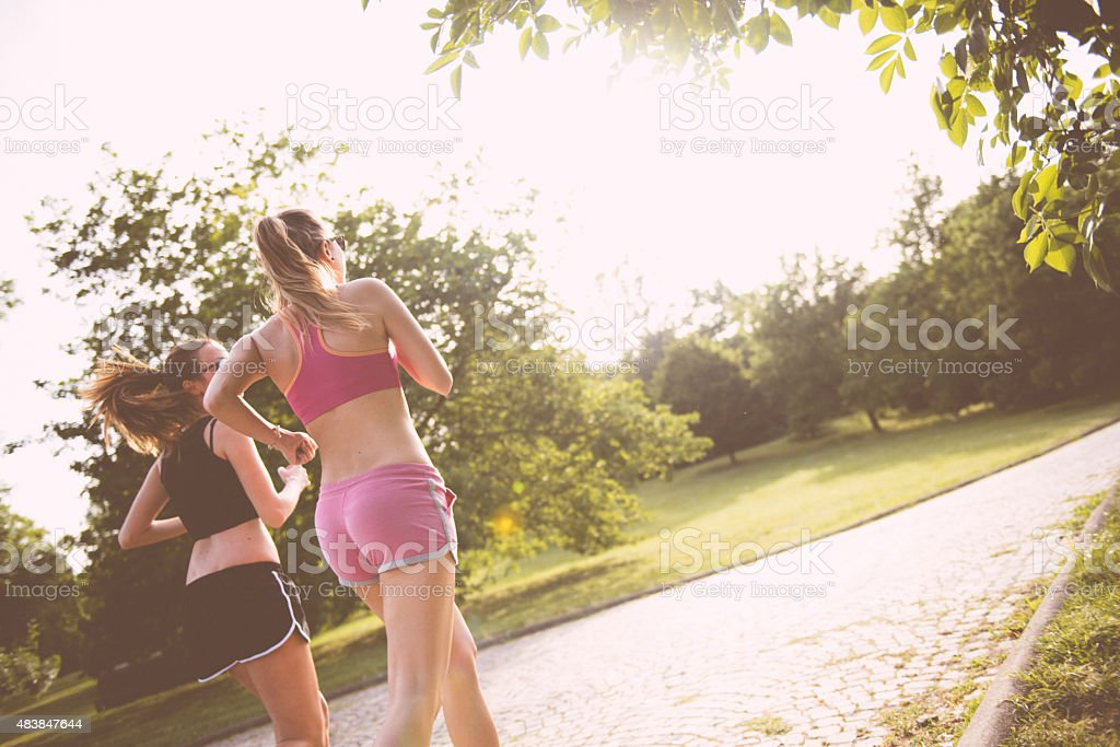 Two woman running at the park stock photo