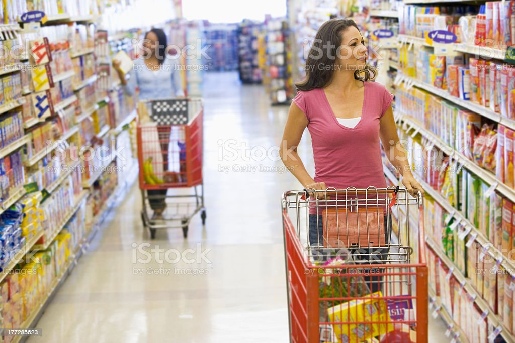 Two woman shopping in same supermarket aisle royalty-free stock photo