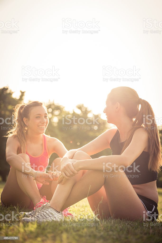 Two woman stretching at the park stock photo