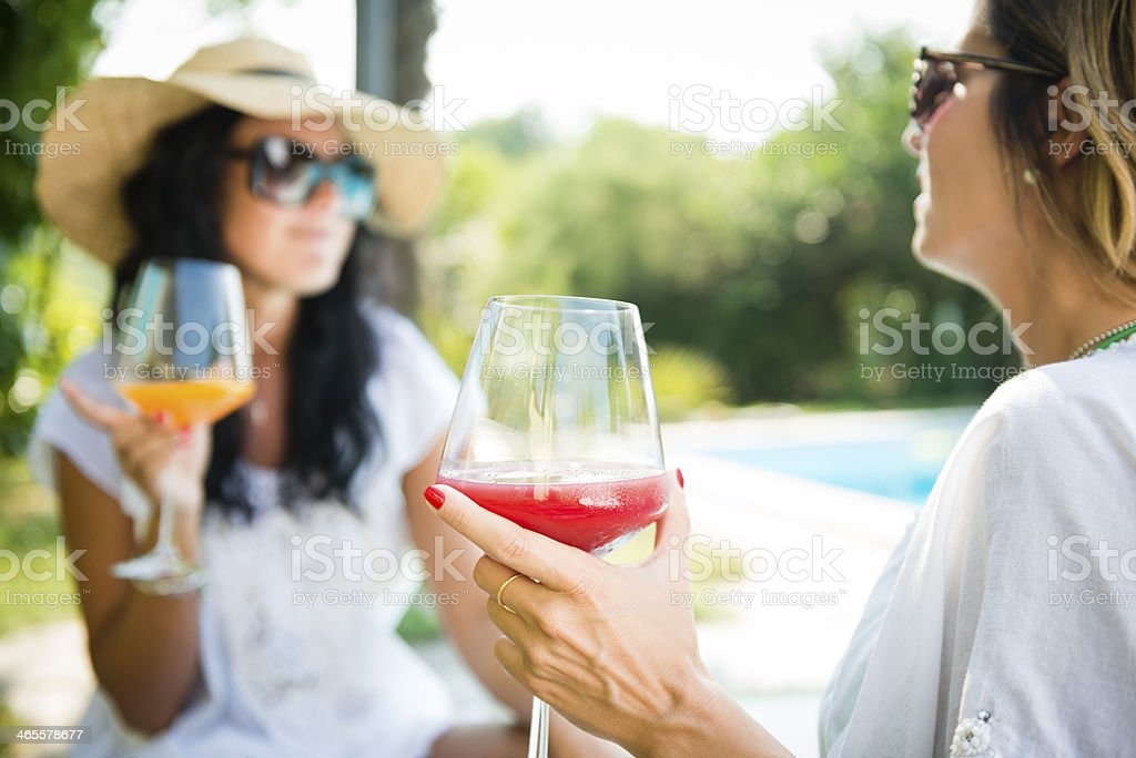 Two woman toasting near the swimming pool royalty-free stock photo