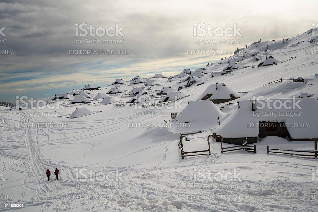 Two woman walking in snow landscape of Velika Planina, Slovenia stock photo