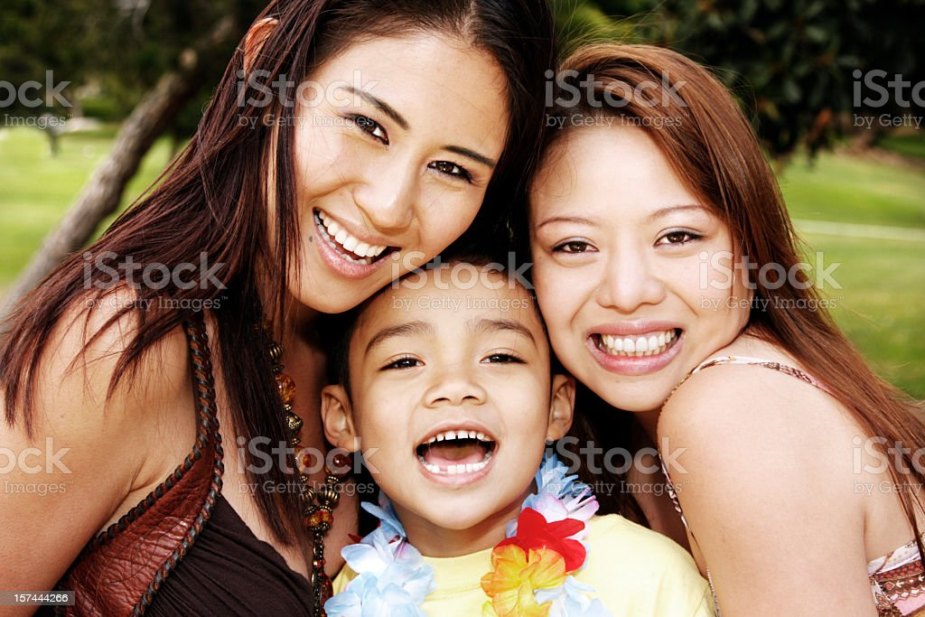 Two women and a boy smiling at the camera royalty-free stock photo