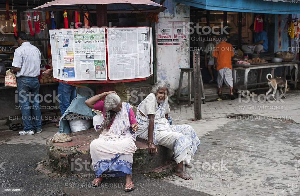 Two women and a free newspaper stand, Kalighat, Kolkata, India. stock photo