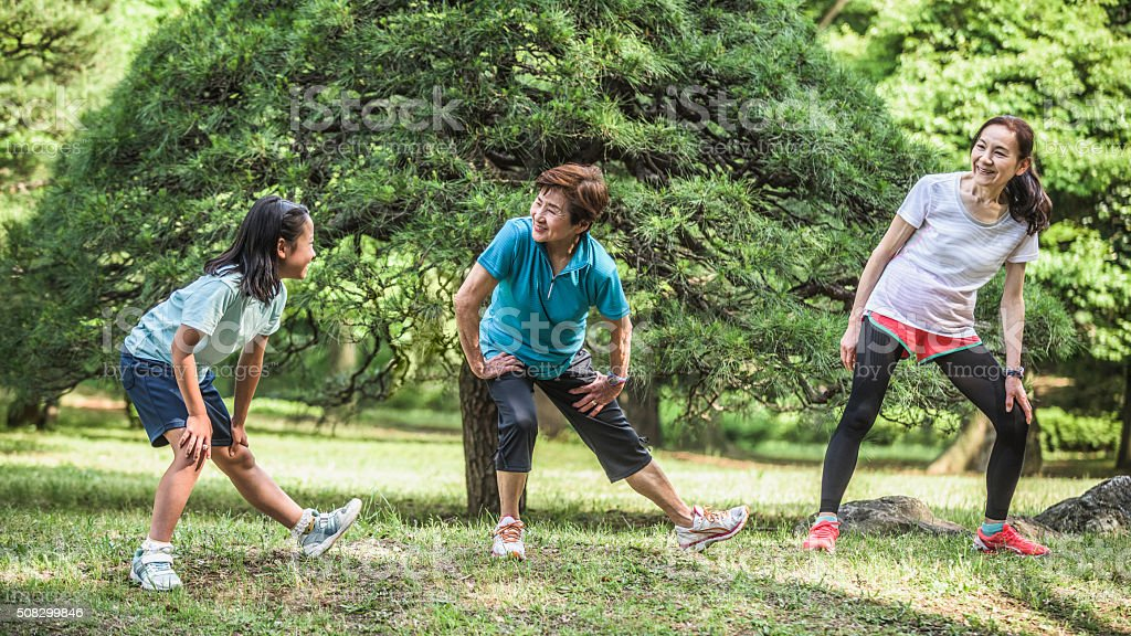 Two women and a girl stretching in park before exercise stock photo