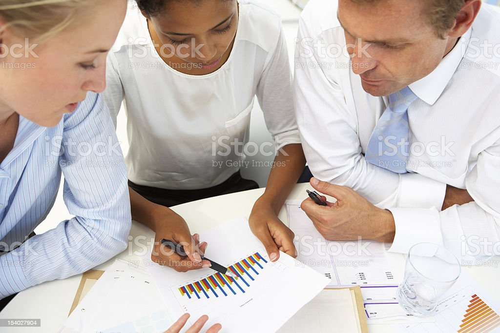 Two women and a man discussing graph results royalty-free stock photo