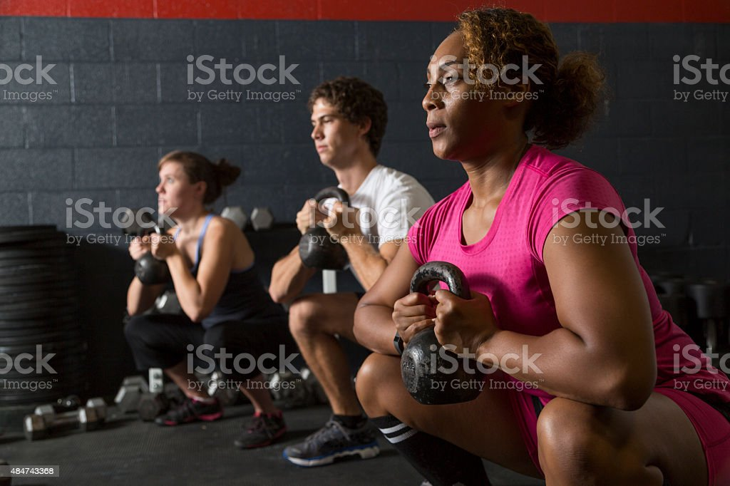 Two Women and a Man Doing Kettlebell Squats stock photo