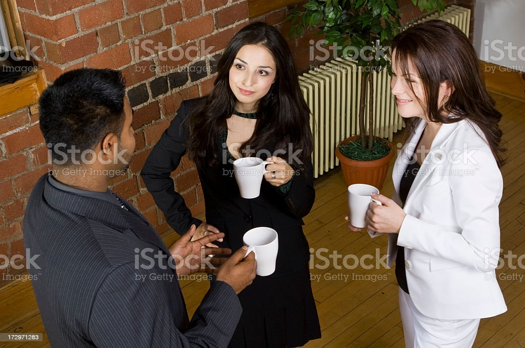 Two women and a man drinking coffee and discussing ideas royalty-free stock photo