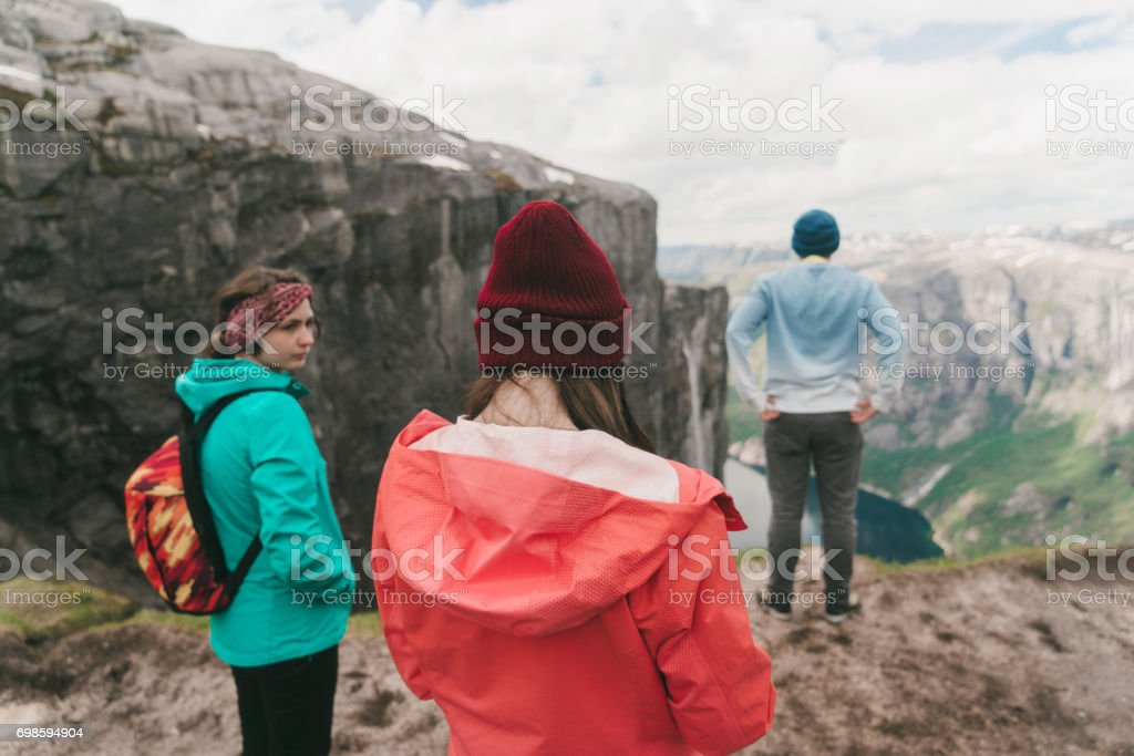 Two women and man looking at Lysefjorden from Kjerag mountain stock photo