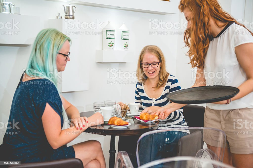 Two Women and Waitress at the Coffee Bar Cafe Trieste stock photo