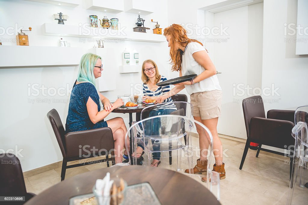 Two Women and Waitress at the Coffee Bar Trieste, Europe stock photo