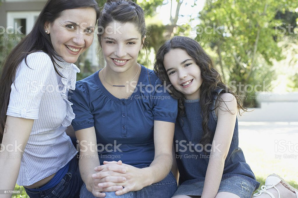 Two women and young girl sitting outdoors smiling stock photo