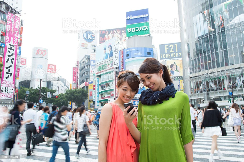 Two women are checking a smartphone at Shibuya crossing stock photo