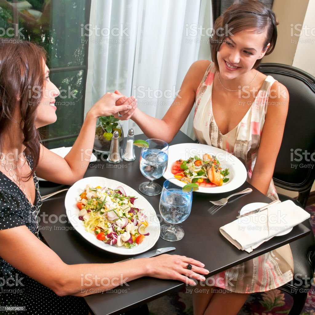 Two women are having dinner at the restaurant - VII royalty-free stock photo