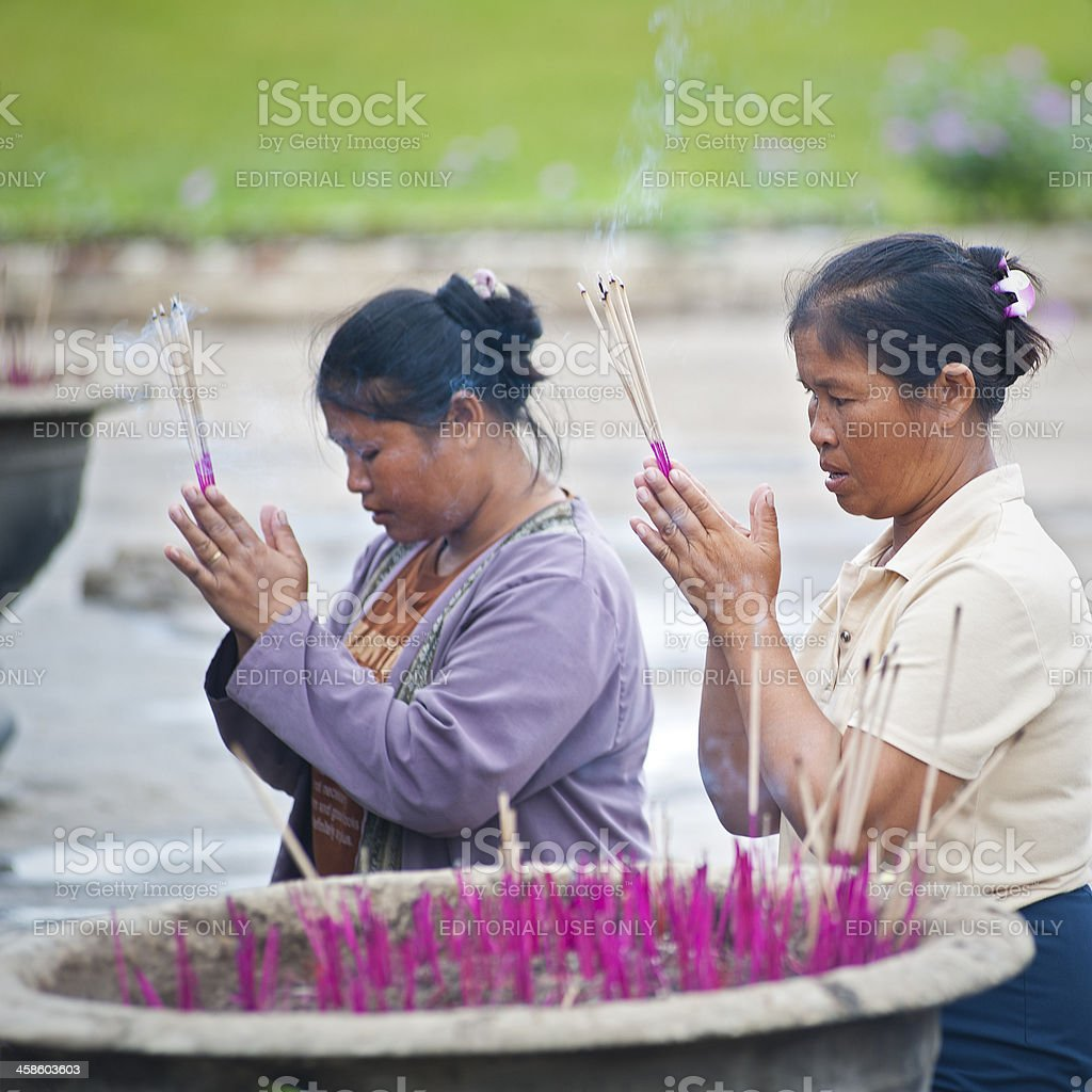 Two women are praying in front of a temple stock photo
