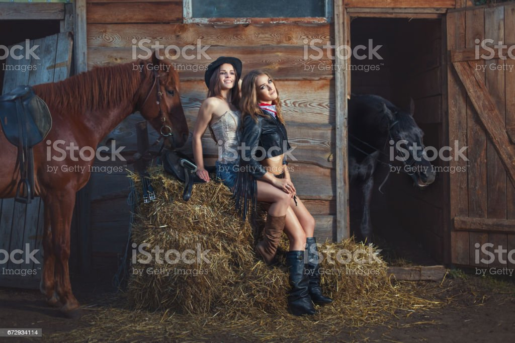 Two women are sitting on a straw on a farm. stock photo