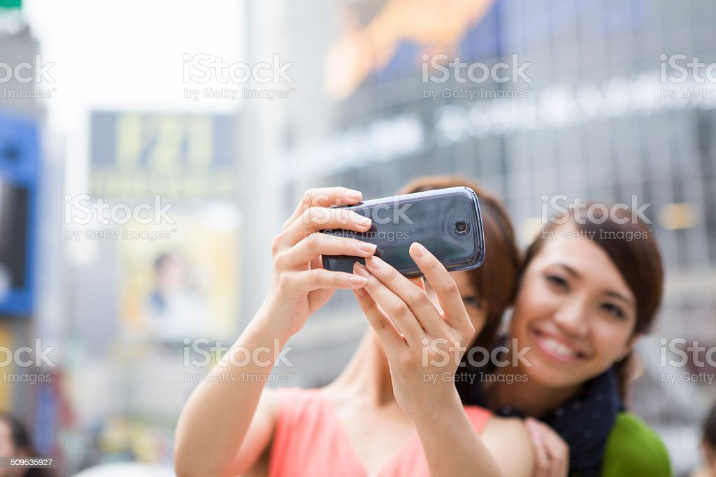 Two women are taking pictures at Shibuya crossing stock photo