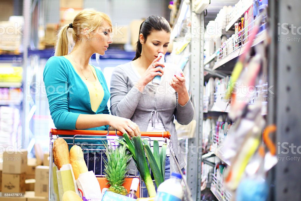 Two women buying cosmetics in supermarket. stock photo