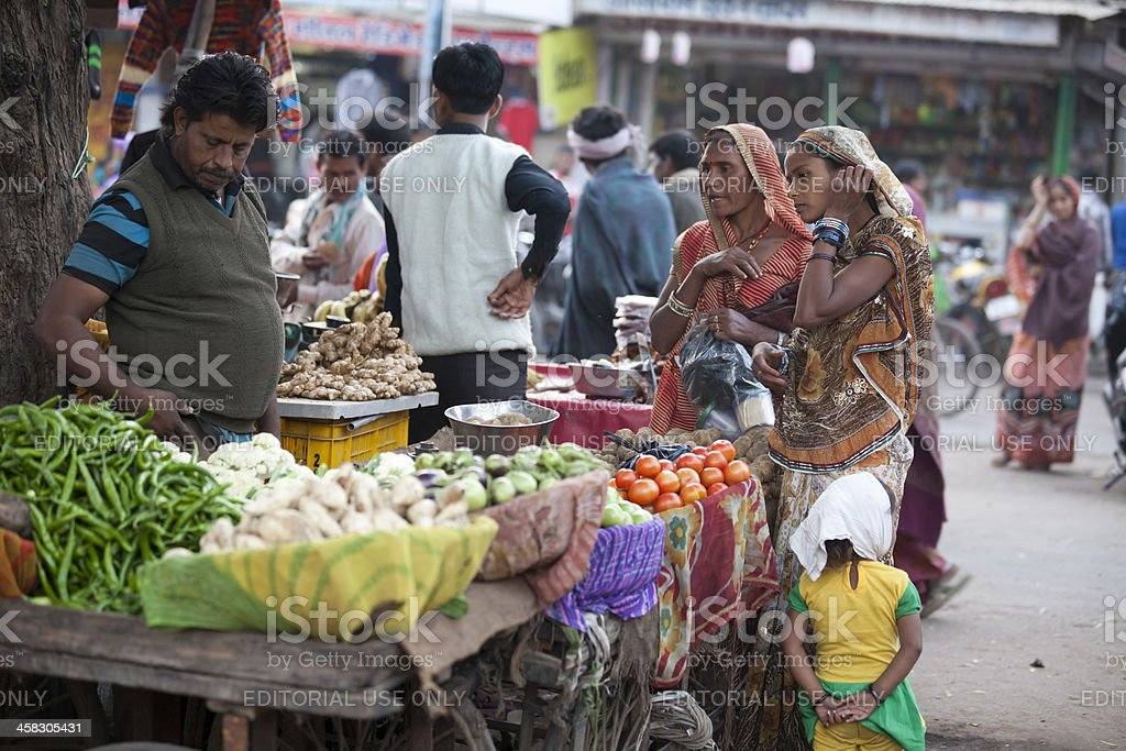 Two women buying in a busy street market, Rajasthan, India royalty-free stock photo