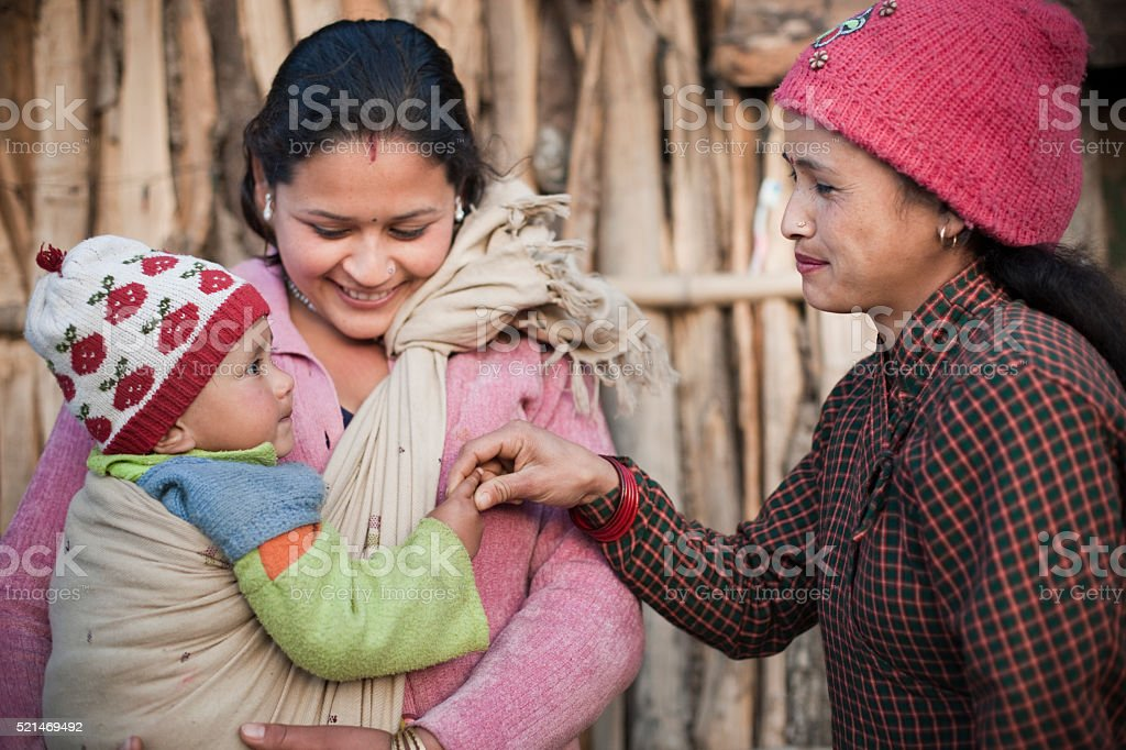 Two women carrying and pampering a preschool child. stock photo