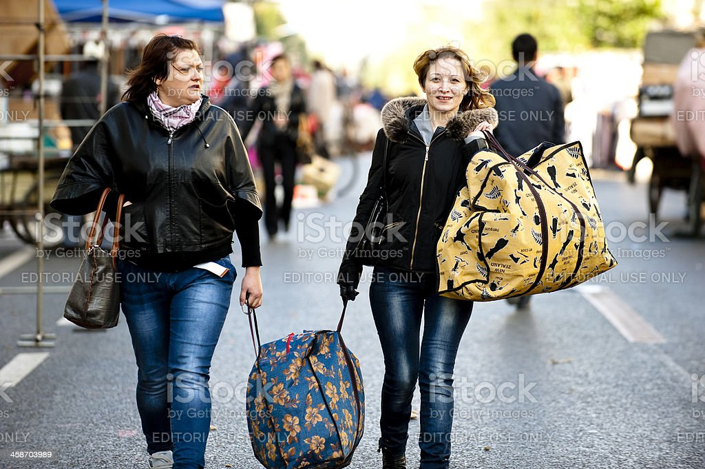 Two Women carrying bag in street market stock photo