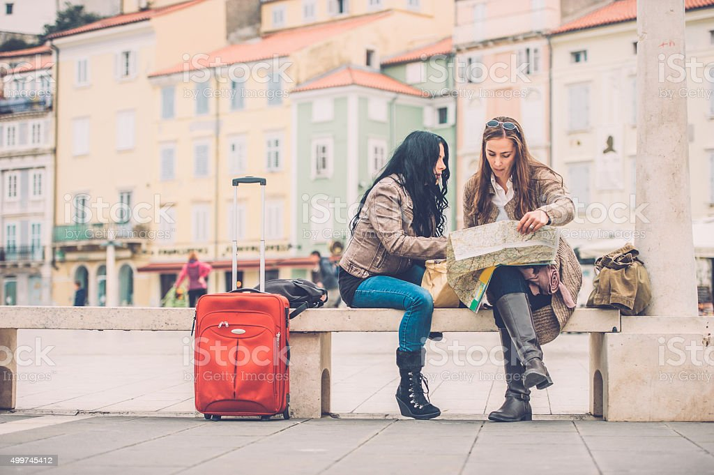 Two Women Checking the City Map, Sitting on a Bench stock photo