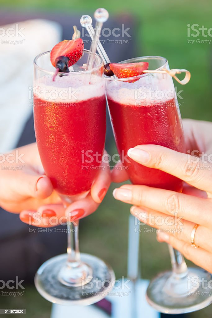 Two women cheering with drinks stock photo