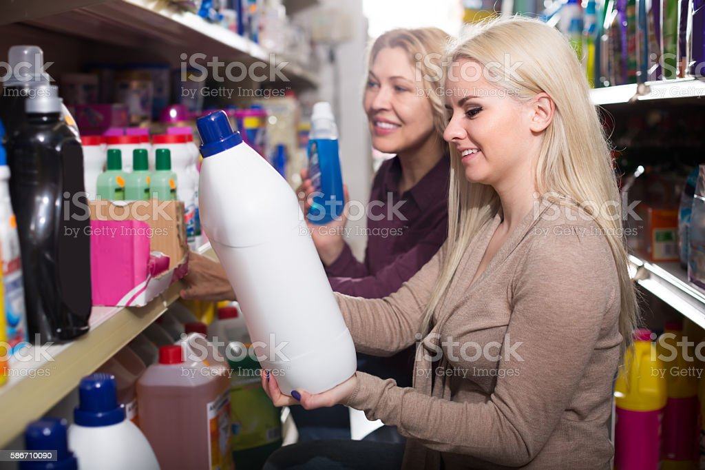 Two women choosing detergents in the shop stock photo
