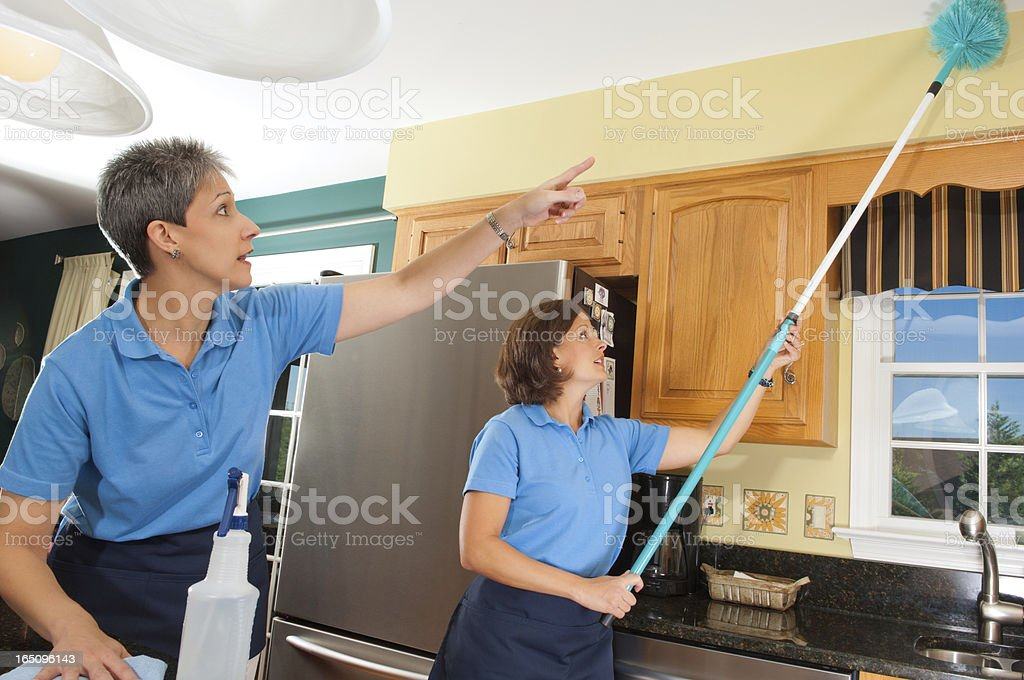 Two women cleaning a kitchen with a long reach duster  stock photo