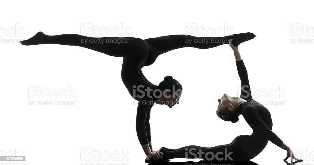 two women contortionist exercising gymnastic yoga silhouette stock photo