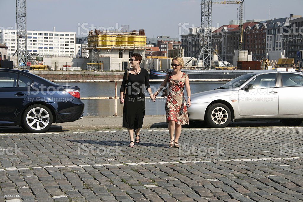 Two women crossing a road stock photo
