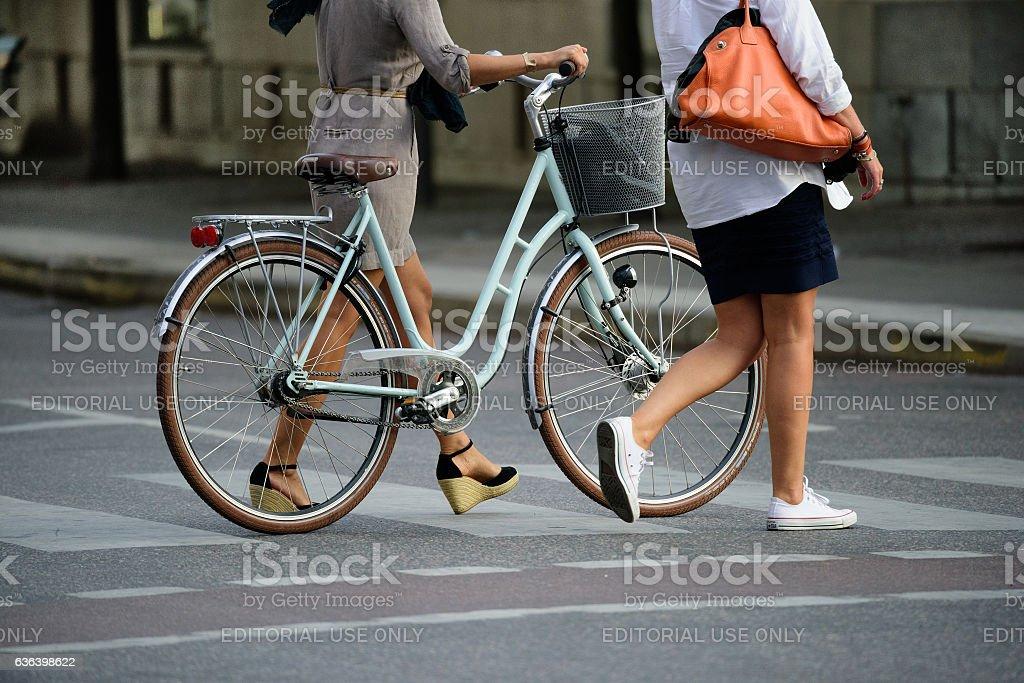 Two women crossing street with bike stock photo