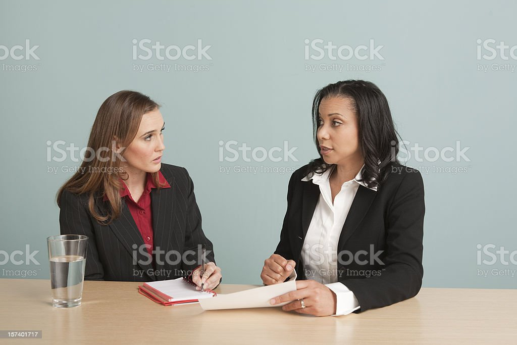 Two women discussing work in a business meeting, taking notes royalty-free stock photo