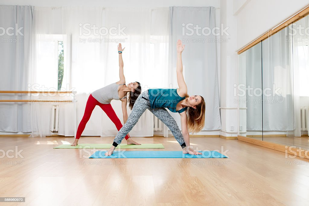 Two women doing extended triangle pose, utthita trikonasana yoga asana stock photo