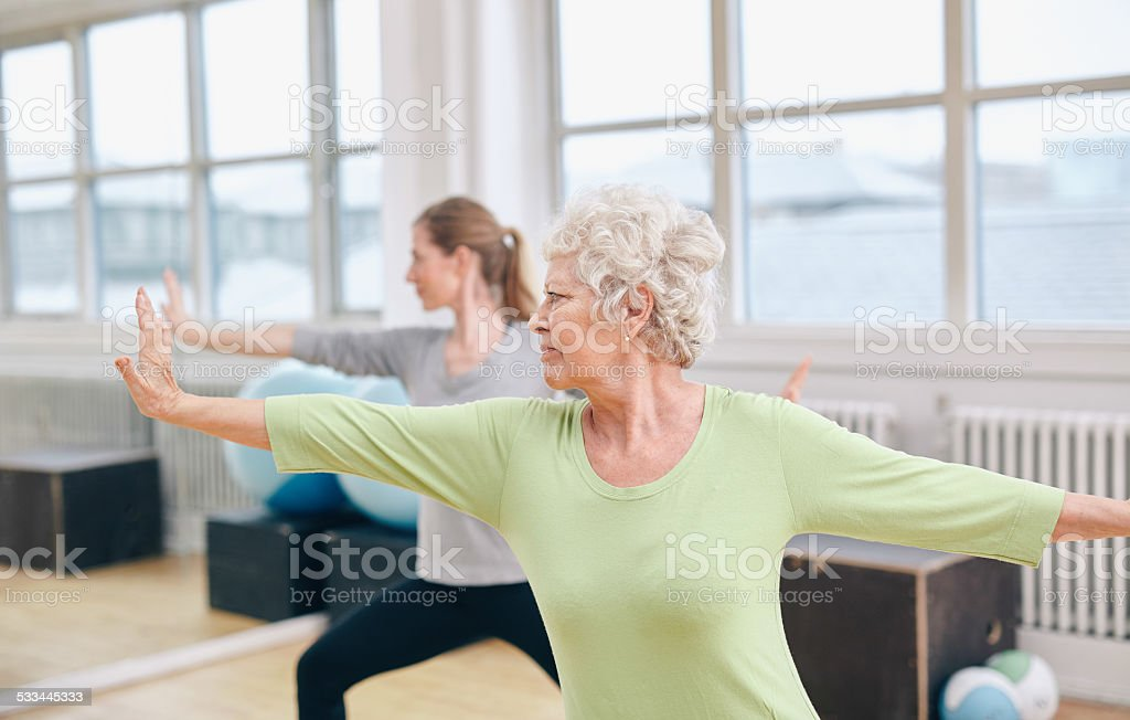 Two women doing yoga workout at gym stock photo