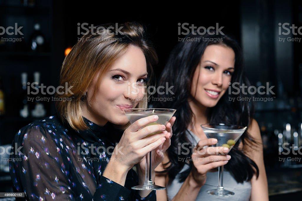 Two women drinking martinis stock photo