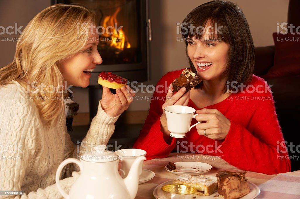 Two women eating afternoon tea in front of a fire stock photo