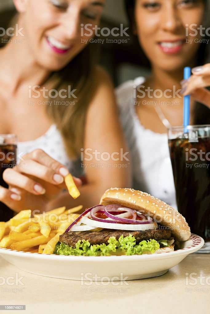 Two women eating hamburger and drinking soda stock photo