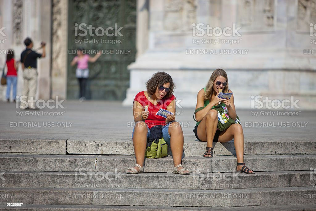 Two women eating ice-cream on stairs of Duomo Cathedral, Milan royalty-free stock photo