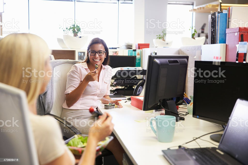 Two women eating lunch at work stock photo